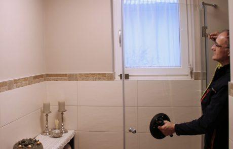 Emmerich Kovacs montiert eine Glastür in einer Dusche